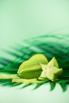 Exotic star fruit or averrhoa carambola over tropical green palm leaves on turquoise background.