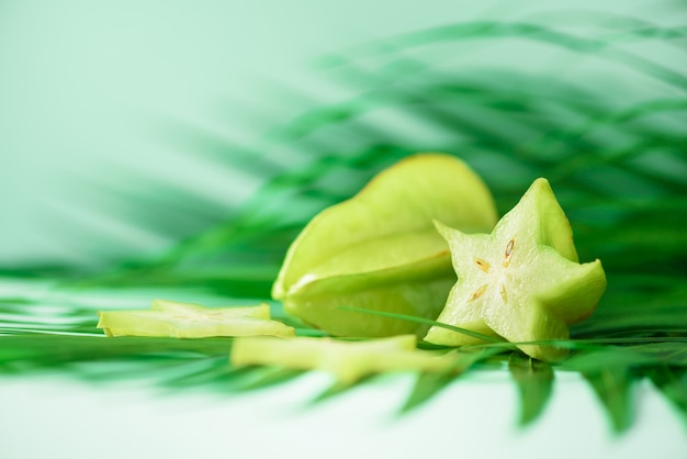 Exotic star fruit or averrhoa carambola over tropical green palm leaves