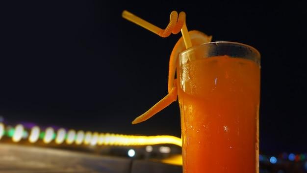 エキゾチックな夏の飲み物、ぼやけた夜の街の景色の背景に対して