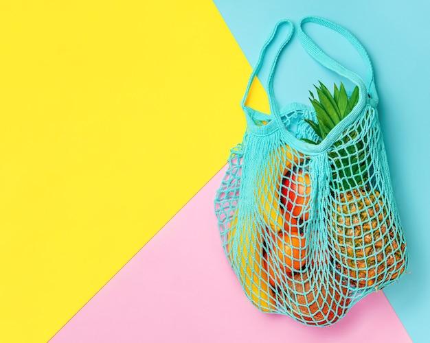 Экзотические летние фрукты в сетчатой сумке на красочном фоне. вид сверху, копия пространства. концепция нулевых отходов
