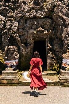 エキゾチックな観光。バリ島の聖地の近くを歩きながら長いドレスを着てリラックスした若い女性