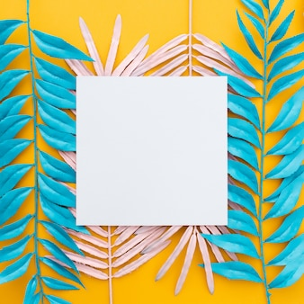 Exotic tropical leaves and blank paper on yellow
