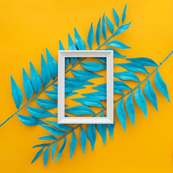 Exotic tropical leaves and empty frame on yellow