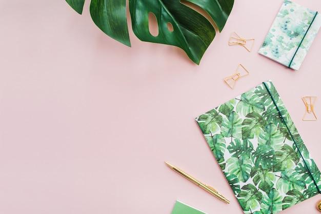 淡いピンクの背景にエキゾチックな熱帯モンステラのヤシの葉とホーム オフィスの文房具。フラットレイ、トップビュー