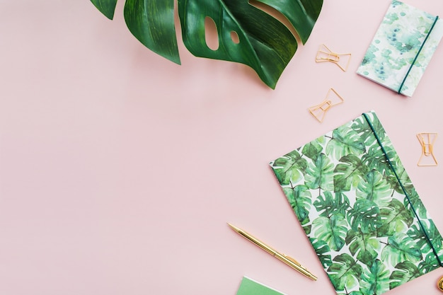 Exotic tropical monstera palm leaf and home office stationery on pale pink background. flat lay, top view