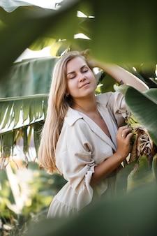 Экзотическая тропическая женщина возле зеленых листьев бананового куста. девушка на тропическом острове в отпуске