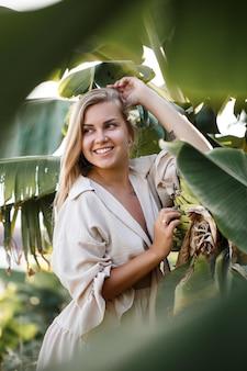 바나나 덤불의 녹색 잎 근처 이국적인 열대 여자. 휴가에 열 대 섬 소녀