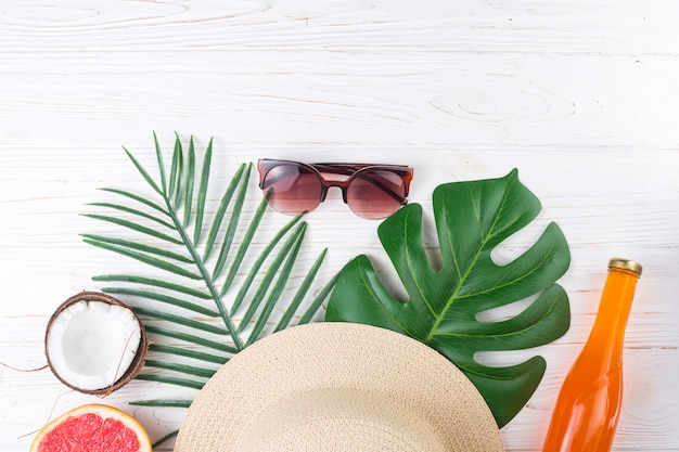 Exotic vacation layout of leaves with sunglasses