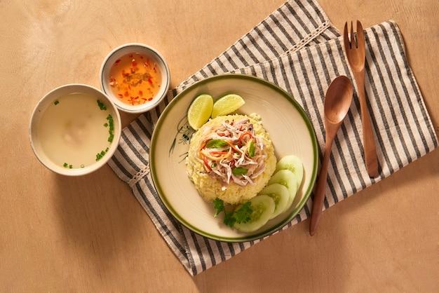 エキゾチックなベトナム料理レストランのメニューをクローズアップ。伝統的なアジア料理を白いプレートで提供。スライスした白鶏肉、青キュウリ、にんじんとご飯
