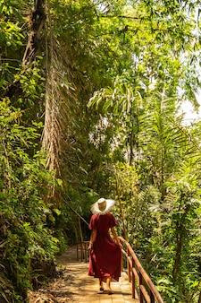 이국적인 전망. 산책하는 동안 모자를 쓰고 발리 여행을 즐기는 기뻐하는 소녀 스톡 사진
