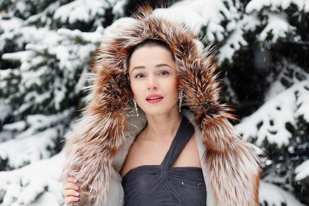 짧은 머리, 뷰티 스타일 초상화를 가진 이국적인 여자. 눈과 긴 눈 덮인 전나무를 배경으로 겨울에 웃고, 귀엽고, 생각에 잠긴 대머리 여성. 이브닝 드레스를 입고 포즈를 취하는 여자
