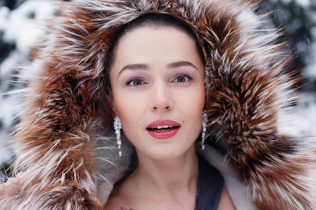 Экзотическая женщина с короткими волосами, портрет стиля красоты. улыбающаяся, милая, задумчивая лысая женщина зимой на фоне снега и длинных заснеженных елей. женщина позирует в вечернем платье