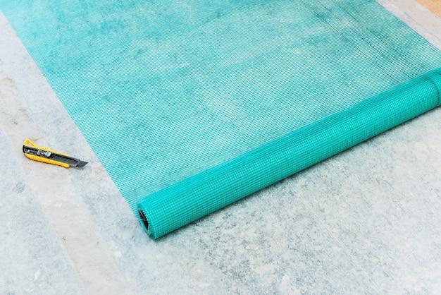 Расширенный рулон стекловолоконной сетки и резак на сером фоне