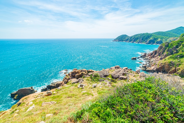 Expansive view of scenic tropical bay, lush green woodland and blue waving sea. the easternmost coast in vietnam, phu yen province between da nang and nha trang.