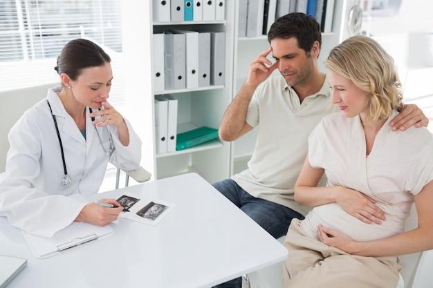 Беременные пара и врач обсуждают отчеты