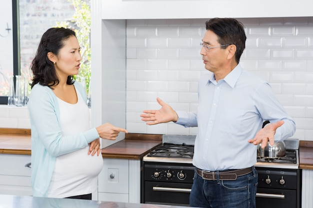 Expectant couple having argument in the kitchen