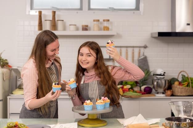 焼きたてのペストリーを食べながら一緒に楽しい時間を過ごして、台所のテーブルでカップケーキを飾る妊婦と娘