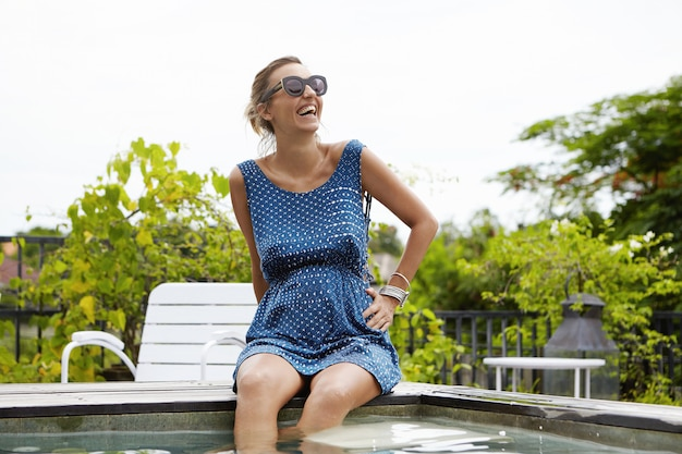 Будущая мама в солнечных очках радостно улыбается во время отдыха в бассейне, свесив ноги под водой, освежается в жаркий летний день