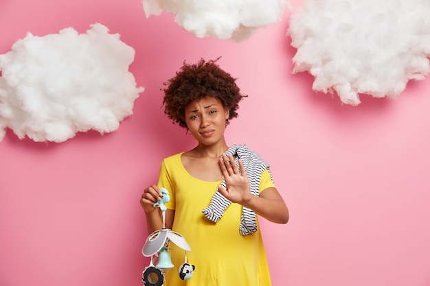 Expectant mother makes refusal gesture, keeps palm in rejection, has pregnant round tummy, poses with baby stuff against pink wall with white clouds. parenting and motherhood.