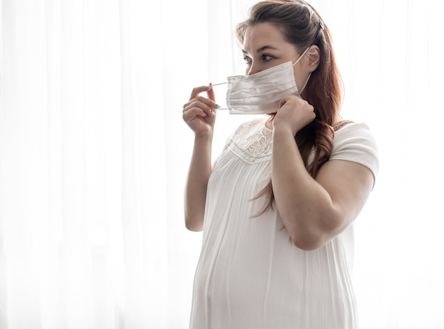 The expectant mother in a white t-shirt with a protective mask against the coronavirus on her face.
