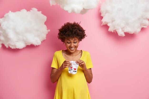 기쁜 표정으로 기대하는 어머니는 작은 아기 양말을보고, 출산을 기다리고, 임신을위한 노란 드레스를 입고, 분홍색 벽에 고립 된 신생아를 기대합니다. 행복 한 임신 개념