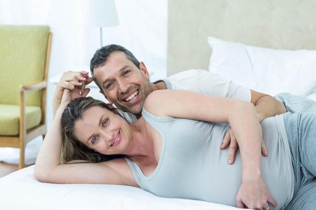 彼らの寝室でベッドに横になっているカップルを期待しています。