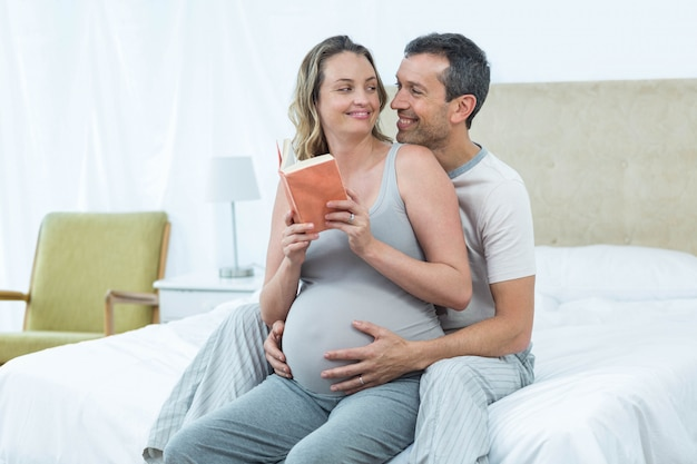 Expecting couple sitting on bed and reading book