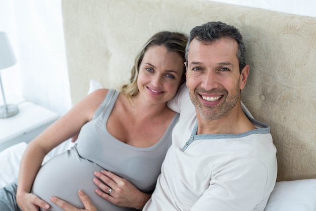 Expecting couple sitting on bed in their bedroom