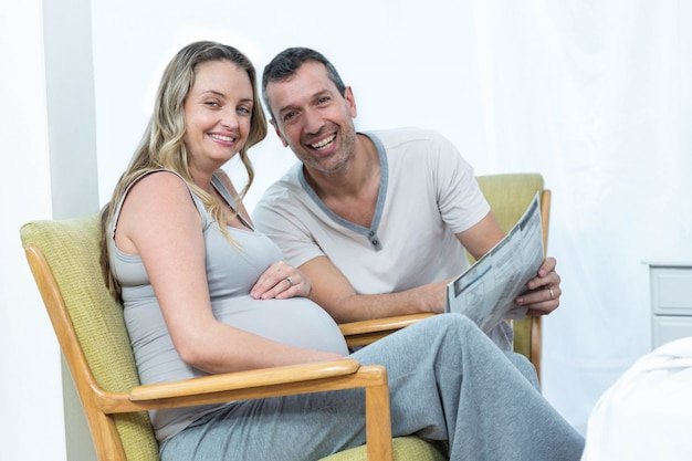 Expecting couple sitting on chair and reading news paper