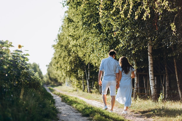 Expecting man and woman walk along the path across the field with sunflowers