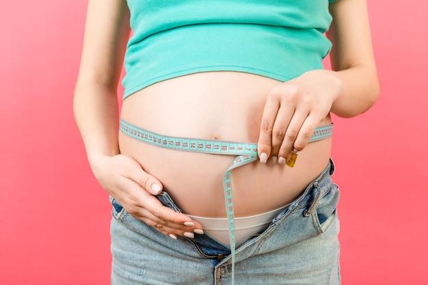 그녀의 임신 배꼽을 측정하는 압축이 풀린 청바지에 기대하는 어머니