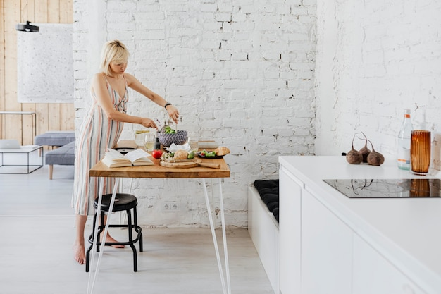 Expecting mother preparing salad in the kitchen