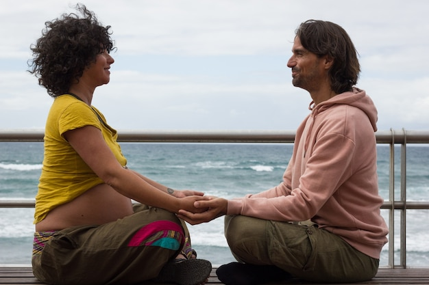Expecting parents holding hands sitting on lotus pose on bench by beach in las palmas