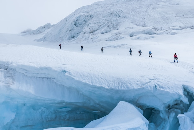 Экспедиция туристов в заснеженных крутых горах