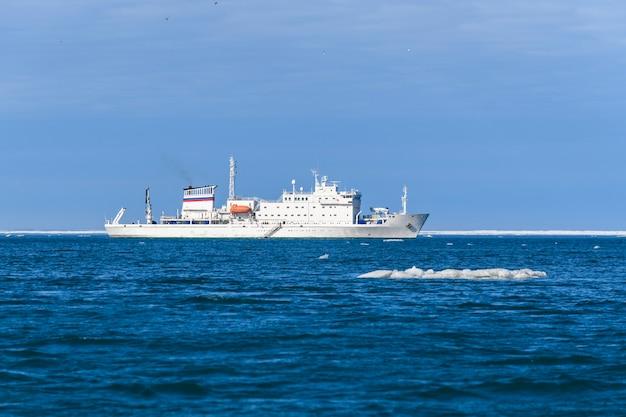 얼음이 있는 북극해의 탐험선. 흰색 연구 선박입니다. franz josef land 군도의 tikhaya bay(tikhaya bukhta)에 있습니다.
