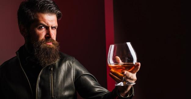 高価な飲み物。ブランデーやコニャックを飲む革のジャケットの男性。ウイスキーのガラスを持つひげを生やした男。