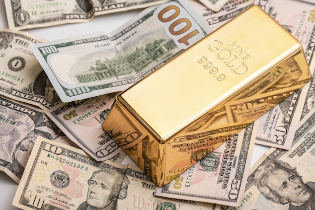 Дорогой золотой слиток и долларовые купюры