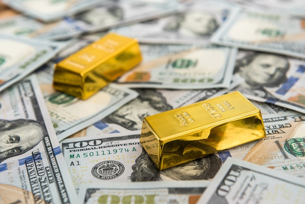 Expensive gold bar lying on dollar bills save money concept