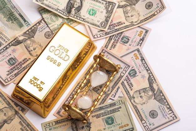 Дорогой золотой слиток, долларовые купюры и песочные часы