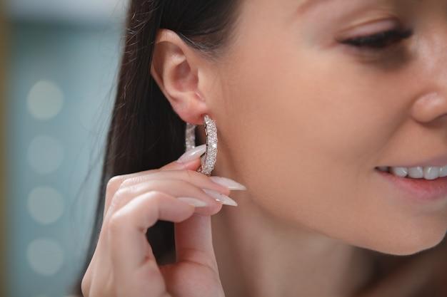 여자의 귀에 비싼 후프 귀걸이