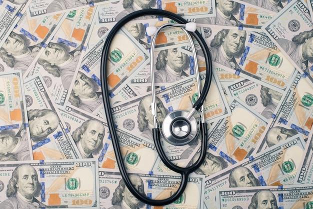 Дорогая медицина или концепция мирового экономического коллапса. фотография стетоскопа доктора, лежащего на стопке американских денег, сверху сверху