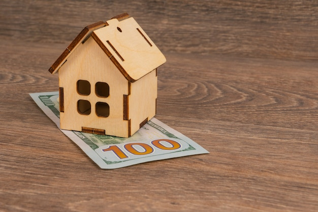 Expensive utilities cost concept with wooden house model and 100 dollar banknotes