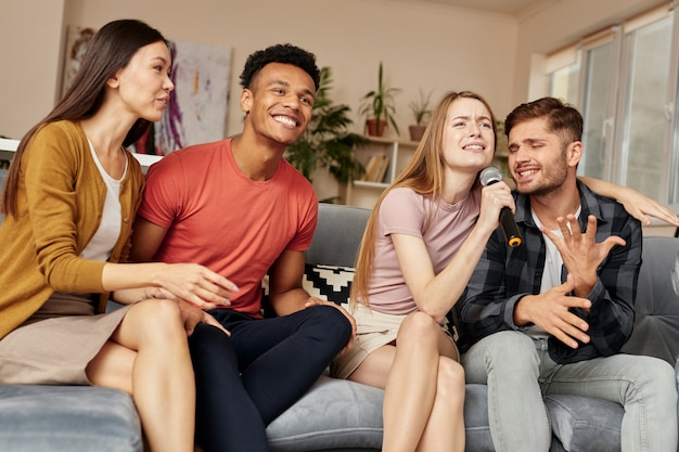自宅でカラオケをしている幸せな若い多文化の友達と一緒にカラオケを体験してください