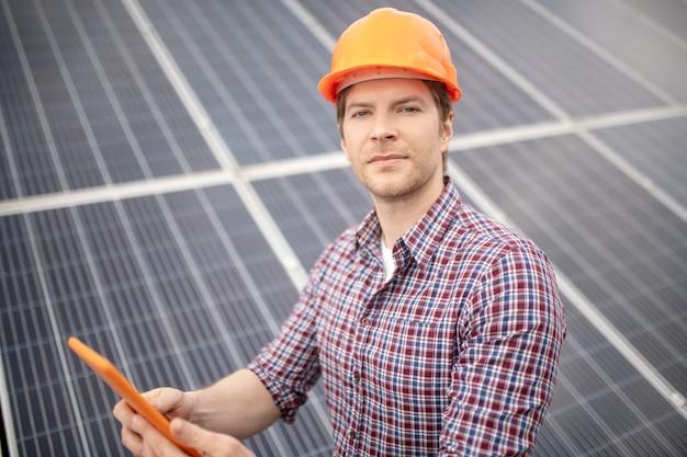 Опыт, знания. опытный рабочий-мужчина в защитном шлеме с планшетом смотрит спокойно и уверенно на фоне серой поверхности здания