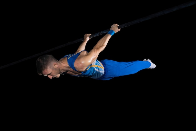 Esperienza. ginnasta maschio muscoloso allenamento in palestra, flessibile e attivo