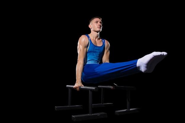 経験。ジムでの筋肉質の男性体操選手のトレーニング、柔軟でアクティブ。白人のフィットの男、強さ、バランスのための運動をしている青いスポーツウェアのアスリート。動き、アクション、動き、ダイナミックなコンセプト。