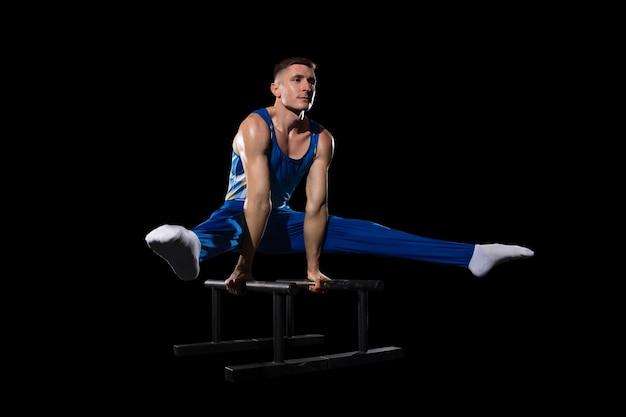 経験。ジムでの筋肉質の男性体操選手のトレーニング、柔軟でアクティブ