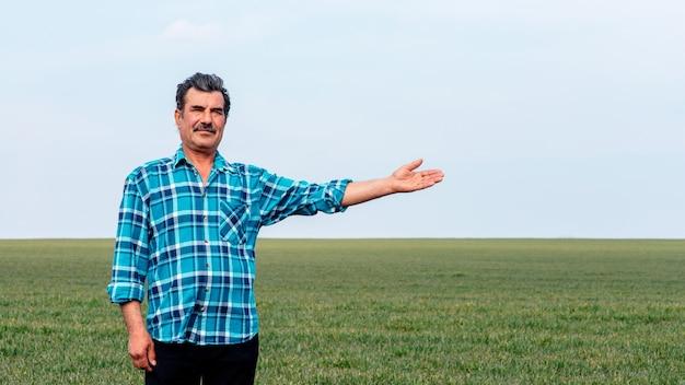Опытный и уверенный фермер стоит на своем поле с протянутой рукой.