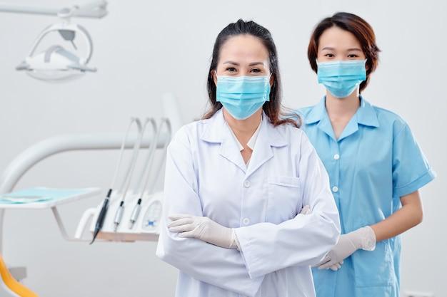 치과 사무실에 서서 카메라를 보고 있는 의료 마스크를 쓴 경험이 풍부한 아시아 치과의사와 간호사