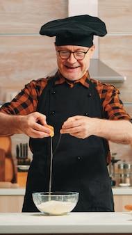 노련한 제빵사는 취미를 즐기는 앞치마를 입고 베이킹을 위해 계란을 크래킹합니다. 수제 케이크를 준비하는 유리 그릇 페이스트리 재료를 반죽하여 손으로 뼈를 섞은 은퇴한 노인 요리사